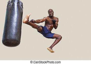 Shirtless muscular boxer kicking punching bag - Full length ...