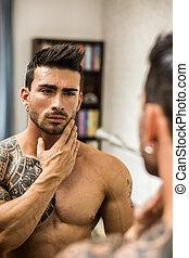 Shirtless muscular handsome man in bedroom