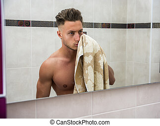 Shirtless muscular handsome young man in bathroom