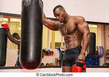 Shirtless muscular male boxer resting next to punching bag