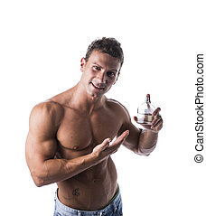 Shirtless muscular male model showing cologne bottle