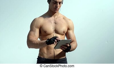 Shirtless muscular man holding tablet computer, standing on...