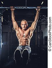 Shirtless muscular man in military pants.