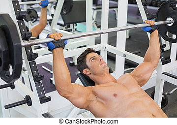 Shirtless muscular man lifting bar - High angle view of a...