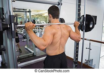 Shirtless muscular man lifting bar - Rear view of a ...