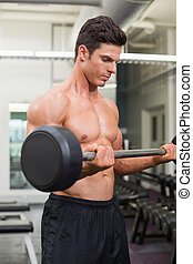 Shirtless muscular man lifting barbell