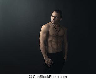 shirtless muscular man looks back