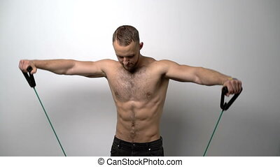 Shirtless muscular man training with Resistance Band - Slow...