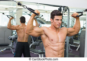 Shirtless muscular man using resistance band in gym -...