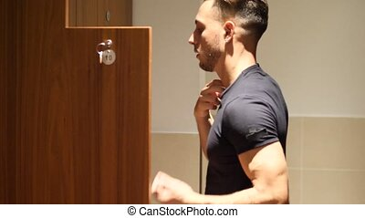 Shirtless muscular young male athlete in gym dressing room -...
