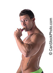 Shirtless muscular young man eating cereal bar