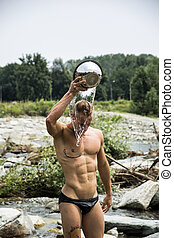 Shirtless muscular young pouring water on his head with...