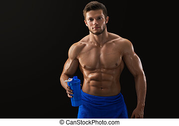 Shirtless ripped sportsman drinking after workout