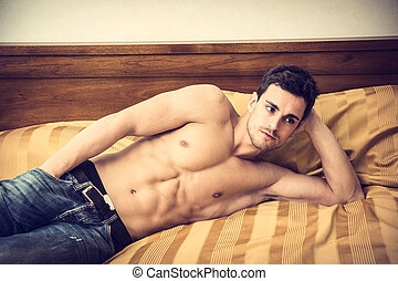 Shirtless sexy male model lying alone on his bed