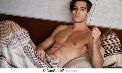 Shirtless sexy male model lying alone on his bed in his...