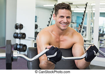 Shirtless smiling bodybuilder lifting heavy barbell weight using