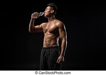 shirtless sportsman drinking water