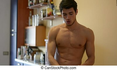 Muscular shirtless young athletic man drinking protein shake from blender, at home in kitchen