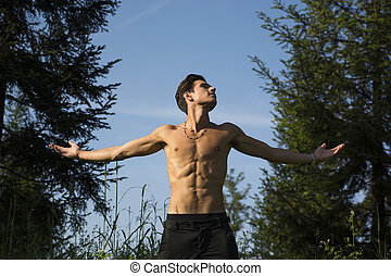 Shirtless young man celebrating nature