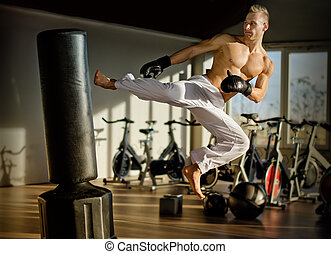 Shirtless young man doing flying kick