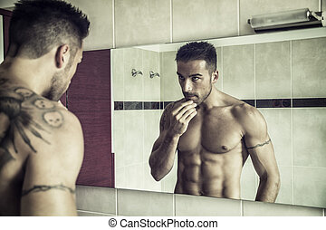Shirtless young man examining his stubble in mirror -...