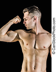 Shirtless young man flexing muscles over black background