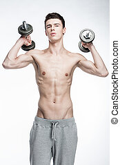 shirtless young man holding dumbbells