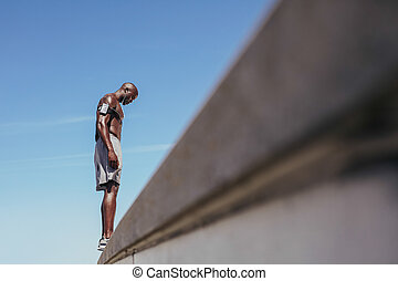 Shirtless young man standing on a wall