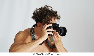Shirtless young man with professional photo camera