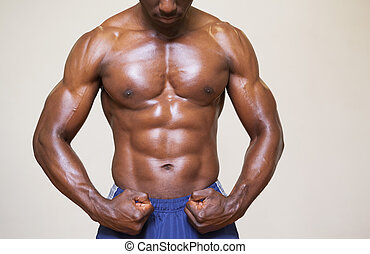 Shirtless young muscular man flexing muscles over white...