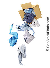 Shirts fall out of a cardboard box isolated on a white background. Donation.
