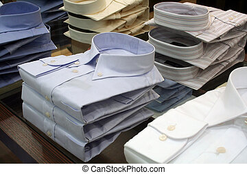 Men's shirts for sale, folded and piled in a department store