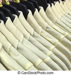 Shirts hanging on a rack in the store.