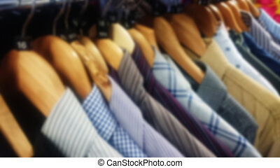Shirts on wooden hangers. Out of focus.