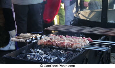 Shish kebab is prepared on the grill grate. - Chef prepares...