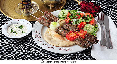 Two shish kebab sticks on pita bread