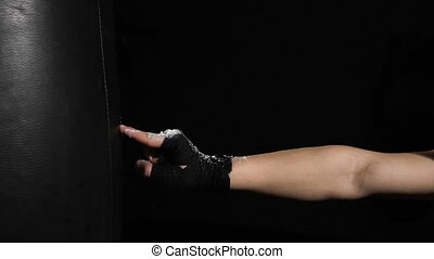 Shock. Hand of boxer and punching bag. Hands in protective bandages