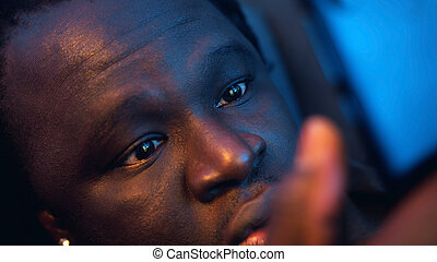 Shocked african american black man reading email wrapped in blanket. Bad news