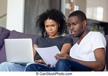 Shocked African American couple receiving bad news, reading letter