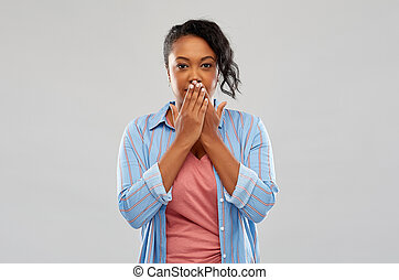 shocked african american woman covering her mouth