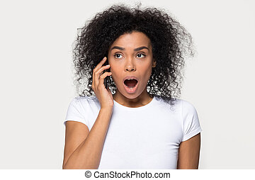 Shocked African American woman talking on phone, hearing unexpected news