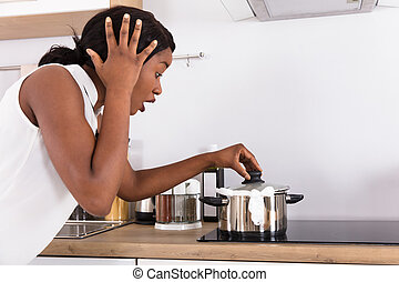 Woman Looking At Spilling Out Boiled Milk From Utensil