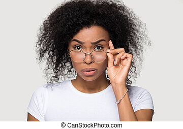 Shocked african young woman lowering glasses looking at camera