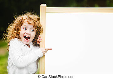 Shocked and happy surprised child with school blackboard.