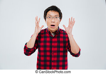 Shocked asian man gesturing with hands over white background