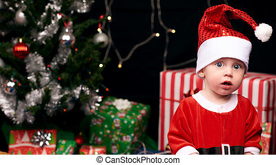 Shocked baby in santa outfit for christmas decorations and tree