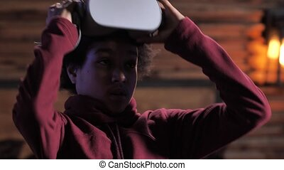 Close-up portrait of overwhelmed teenager taking off augmented-reality headset to exit virtual reality. Mixed race boy shocked by reality of what is happening in virtual world during video game