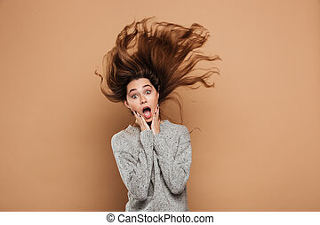 Shocked brunette woman with funny hairstyle touching her face and looking at camera