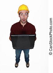 Shocked builder holding laptop