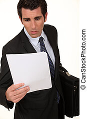 Shocked businessman reading document